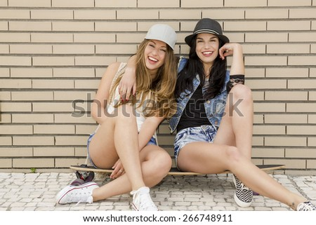 Two beautiful and young girlfriends having fun with a skateboard, in front of a brick wall - stock photo
