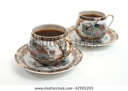 Two beautiful antique cups of coffee, isolated on white