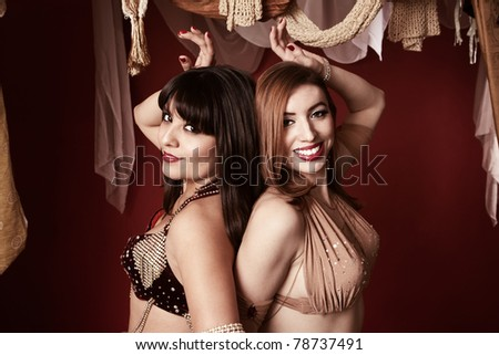 Two beautiful Arab belly dancers with their hand raised