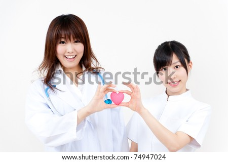two beautiful asian doctors holding symbol of heart - stock photo