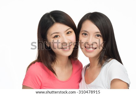 Two beautiful asian girls smiling looking at the camera, isolated on white background.