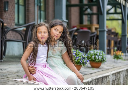 two beautiful asian sisters sitting on the sidewalk - stock photo