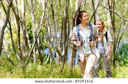 two beautiful attractive woman hiking outdoors in the woods. healthy active lifestyle concept - stock photo