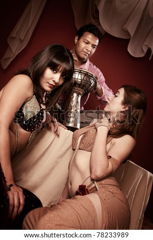 Two beautiful belly dancers look at a handsome Indian tabla player
