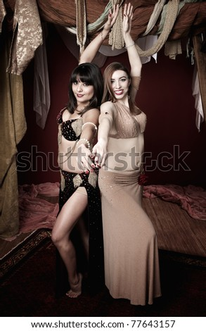 Two beautiful belly dancers pose back to back