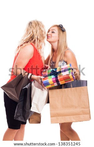 Two beautiful blond girls kissing on the cheek and holding shopping bags with gifts, isolated on white background - stock photo