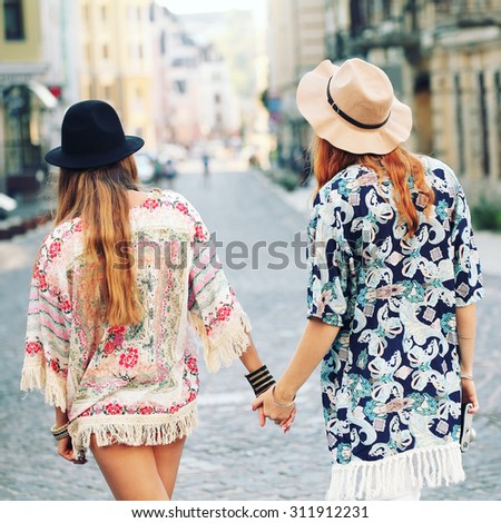 Two beautiful boho girls. Back view.