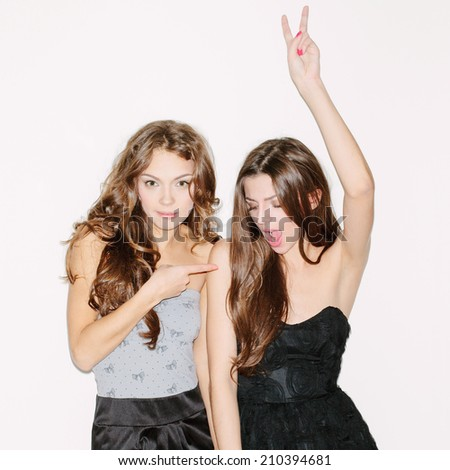 Two beautiful brunette girls having fun. Wearing dresses. One dancing, second looking at camera. Inside - stock photo