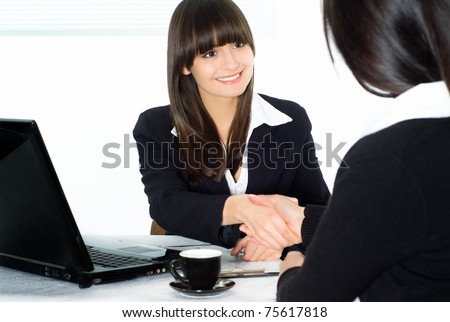 two beautiful business women sitting at the table - stock photo