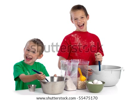 Two beautiful caucasian brothers making a cake in the kitchen, smiling happily, isolated on white background - stock photo