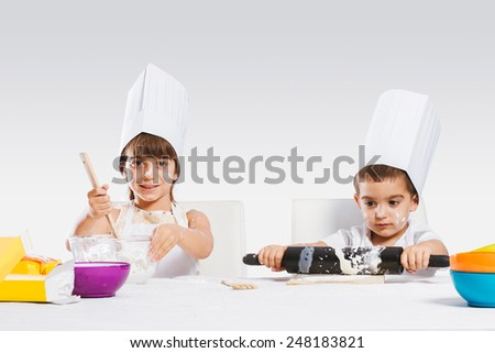 Two beautiful caucasian brothers making a cake, isolated on white background - stock photo
