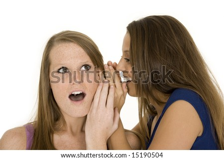 Two beautiful caucasian women telling secret on a white background