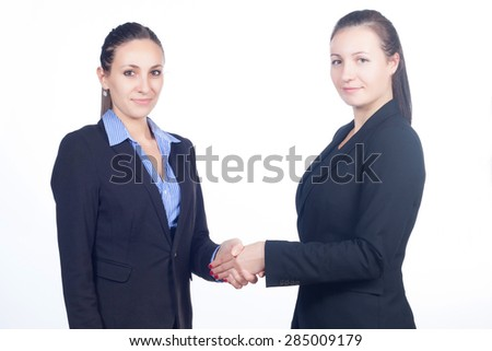 Two beautiful confident business women with crossed arms and shaking hands isolated on white background. Business, finance and education concept.