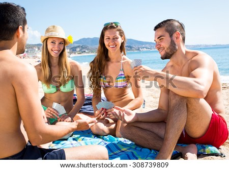 Two beautiful couples playing card games sitting on a towel on a sandy beach near sea - stock photo