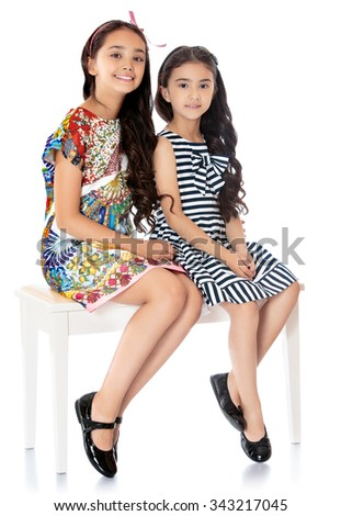 Two beautiful dark-haired girl with Oriental appearance of different ages, posing for the camera. Girl sitting on white couch - Isolated on white background - stock photo