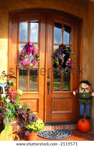 Two beautiful doors adorned with wreaths for Halloween.  A scarecrow and pumpkin await trick or treaters on one side and a flower garden with a happy halloween stake is on the other. - stock photo
