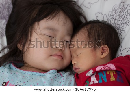 Two beautiful East Asian sister infant and toddler siblings sleeping soundly in bed together - stock photo