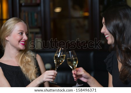 Two beautiful elegant women friends in stylish simple black cocktail dresses toasting each other with glasses of chilled white wine as they celebrate on a night out together