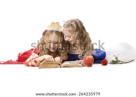 Two beautiful emotional little girls with long blonde hair in the princess costumes reading a magic book at the white background. Red and blue empire dresses - stock photo
