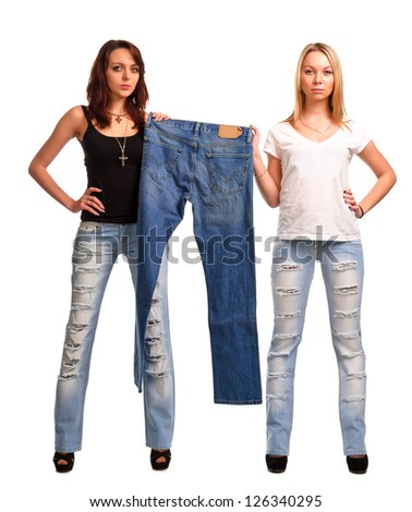 Two beautiful fashion concious women wearing modern raggedy designer jeans holding up a pair of old blue denim jeans on display isolated on white - stock photo
