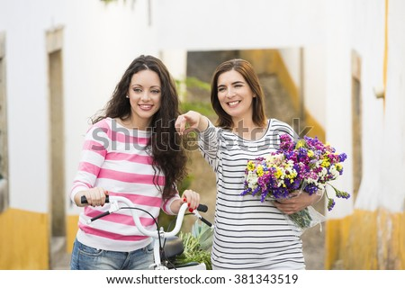Two beautiful female friends smiling and pointing to somewhere - stock photo