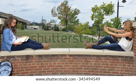 Two beautiful female students together on campus - sitting with books - one studying with glasses on - the other taking a selfie - stock photo