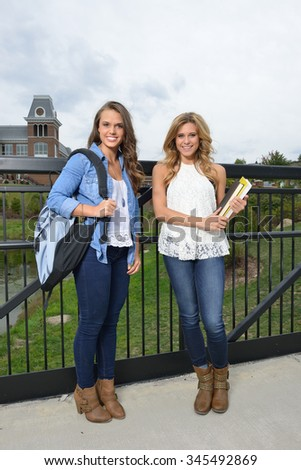 Two beautiful female students together on campus - standing holding books or backpack - stock photo