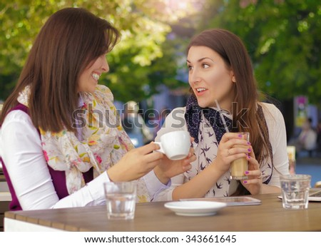 Two Beautiful Females In Cafe Using Digital Tablet