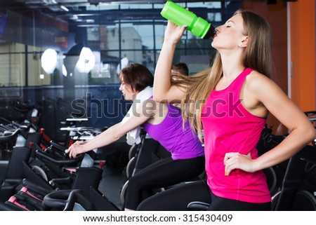 Two beautiful fitness women, wearing in sportswear, doing exercises on bicycles in the gym, girl in pink shirt is drinking water from green bottle, waist up