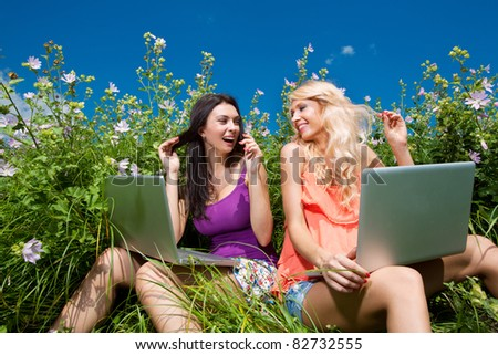 Two beautiful girl on laptop computer outdoors. Sit on green grass. - stock photo
