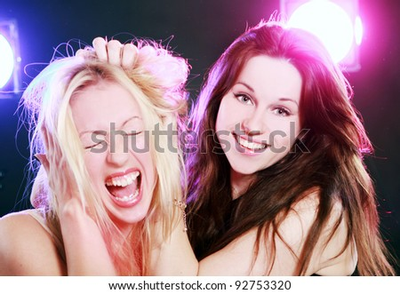 Two beautiful girlfriends in colorful light - stock photo