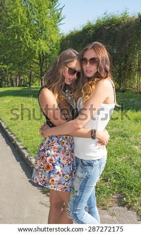 Two beautiful girlfriends relax the summer park  - stock photo