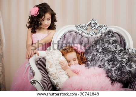 Two beautiful girls, a two children on a chair in a nice dress - stock photo