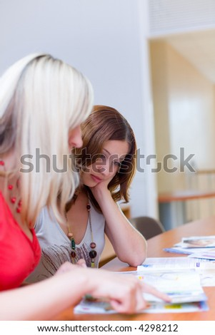 Two beautiful girls are looking through a magazine - stock photo