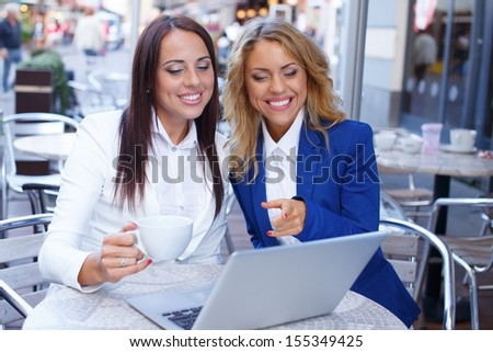 Two beautiful girls cups and laptop in summer cafe