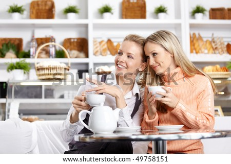 Two beautiful girls discuss something in cafe - stock photo