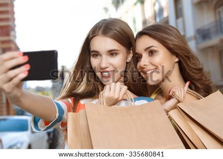 Two beautiful girls doing selfie with shopping bags - stock photo
