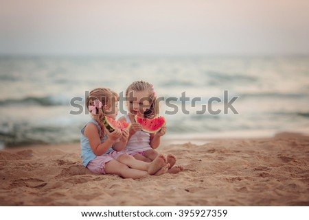 Two beautiful girls eating ripe watermelon on the beach - stock photo