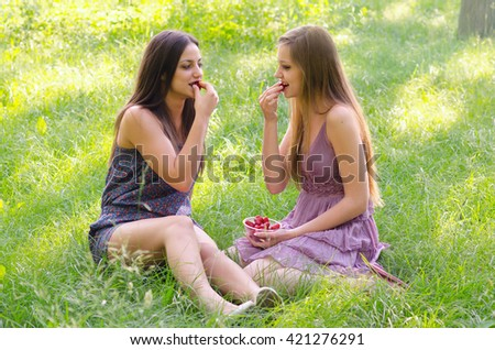 Two beautiful girls eating strawberries in sunny spring nature. - stock photo