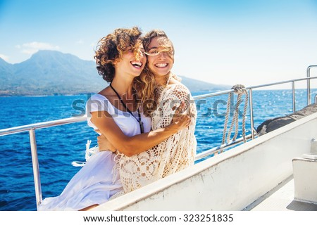 two beautiful girls enjoying a trip on a boat in Bali, Indonesia - stock photo