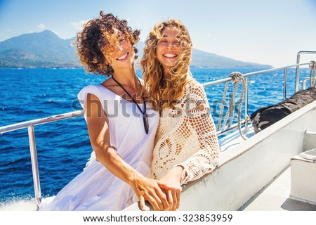 two beautiful girls enjoying a trip on a boat in Bali, Indonesia - stock photo
