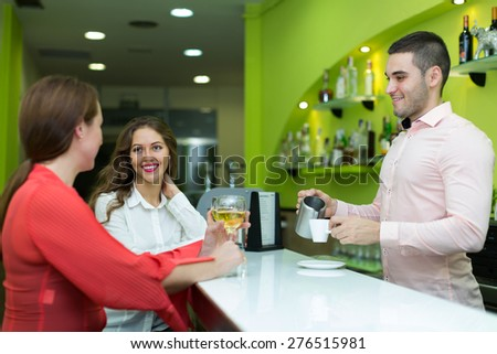 Two beautiful girls flirting with a handsome barman
