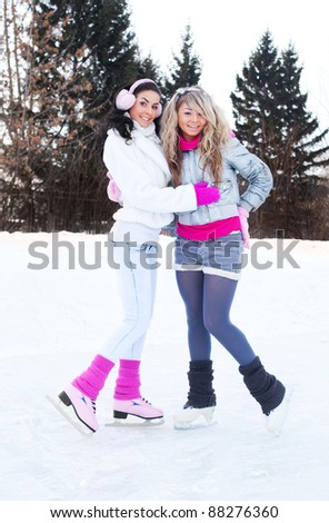 two beautiful girls ice skating outdoor on a warm winter day (focus on the blond girl) - stock photo