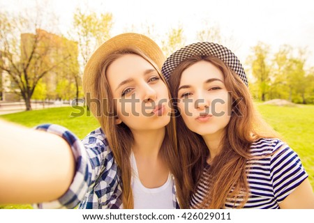 Two beautiful girls in caps making selfie and pouting - stock photo