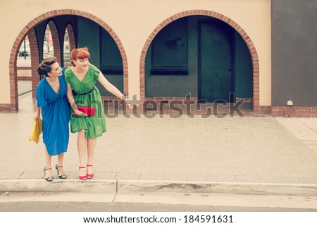 Two beautiful girls in retro style in the street - stock photo