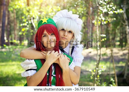 Two beautiful girls in the park. Cosplay characters - stock photo