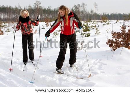 Two beautiful girls in the winter skiing - stock photo