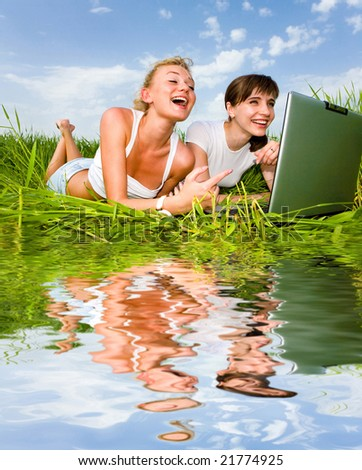 Two beautiful girls in white clothes are laughing and looking at laptop computer outdoors. Lay on the green grass. Reflected in water - stock photo