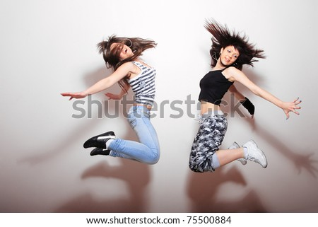 Two beautiful girls jumping against wall - stock photo