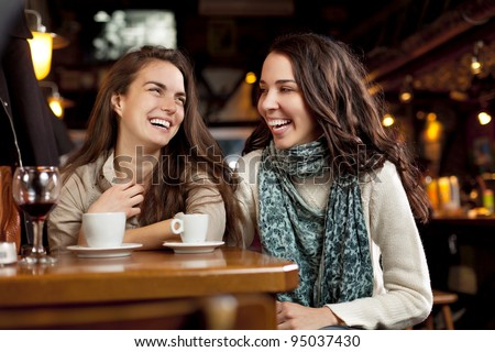 Two beautiful girls laughing in a cafe bar - stock photo